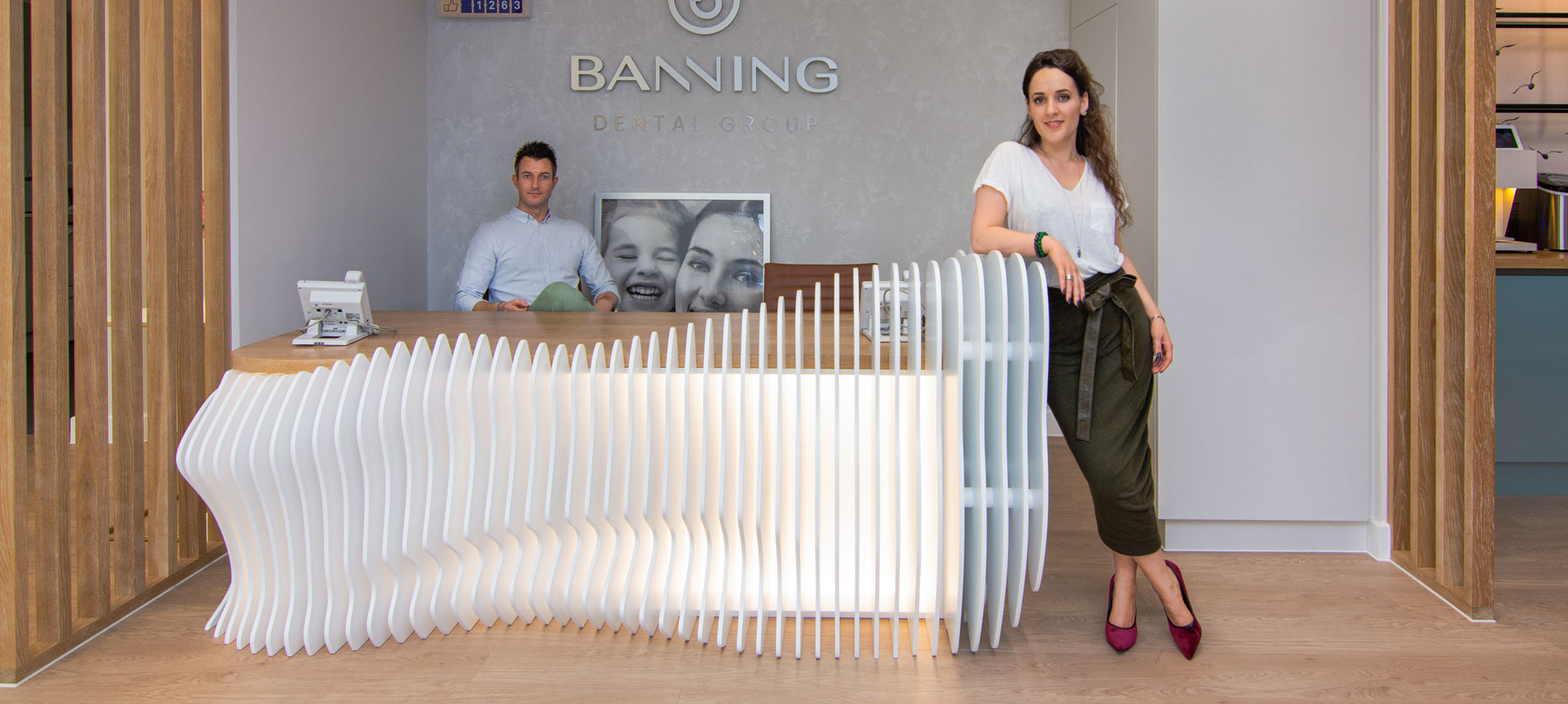 Our founders Reni (standing) & Marc (sitting) are design experts in both office and dental design they are photographed by the bespoke tooth-shaped reception desk at a Banning Dental office