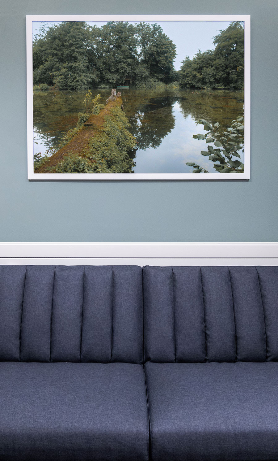 A close up photograph of the grey sofa with a framed photograph of a lake landscape at the 1account office