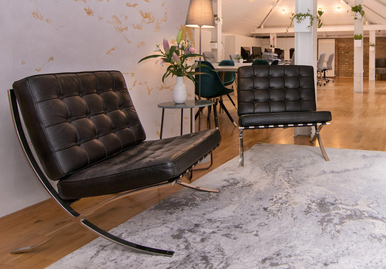 The two leather chairs as part of the Avalon commercial interior design reception seating area with a stand up lamp and a luxury white and gold leaf wallpaper