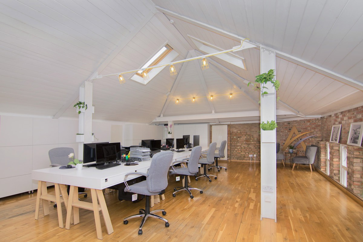 An overview of the Avalon workspace highlighting the main office desk central to the room with natural light beaming from the skylights above