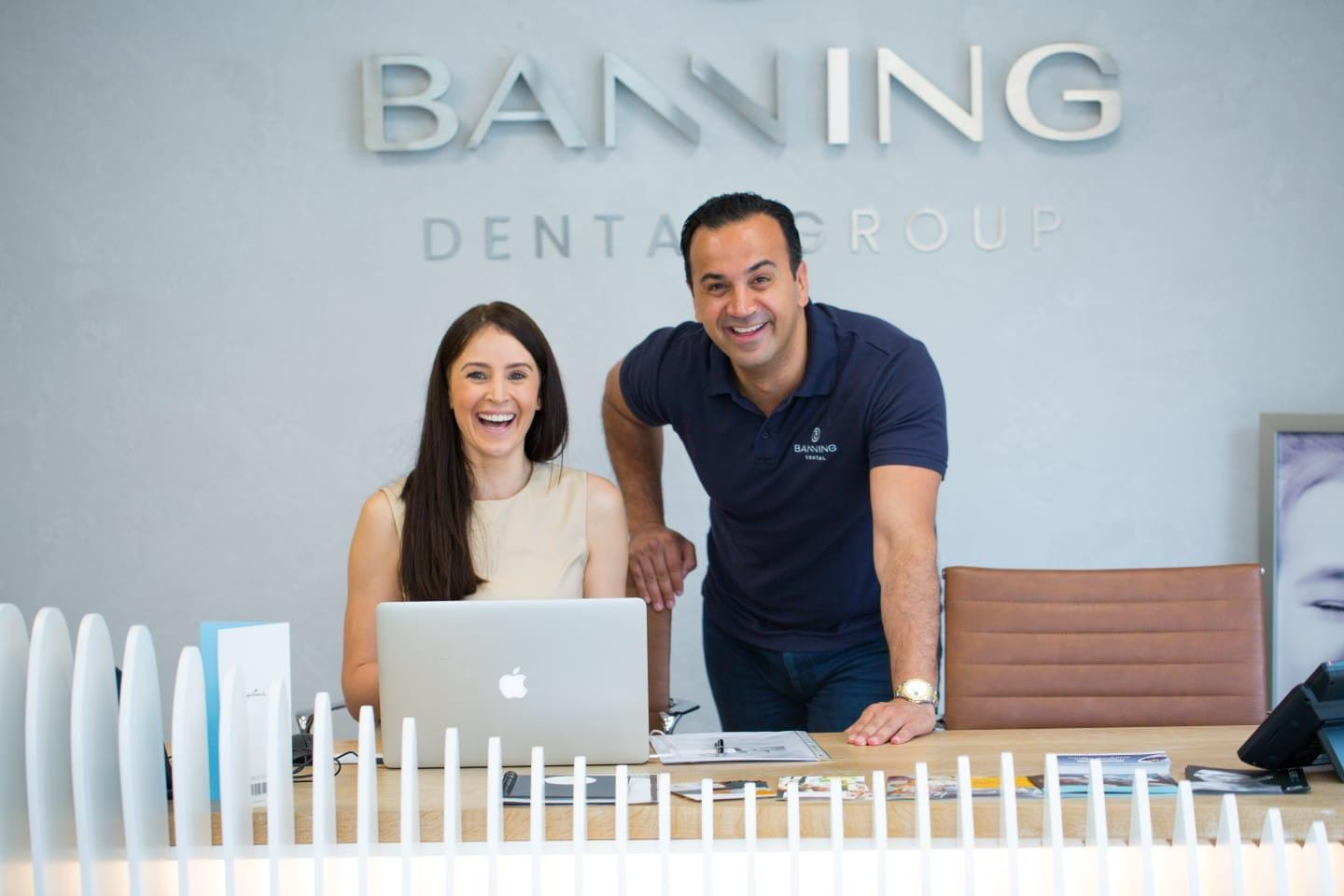 Team at Banning Dental Group smiling at the reception desk as they enjoy their new commercial interior design & fit-out
