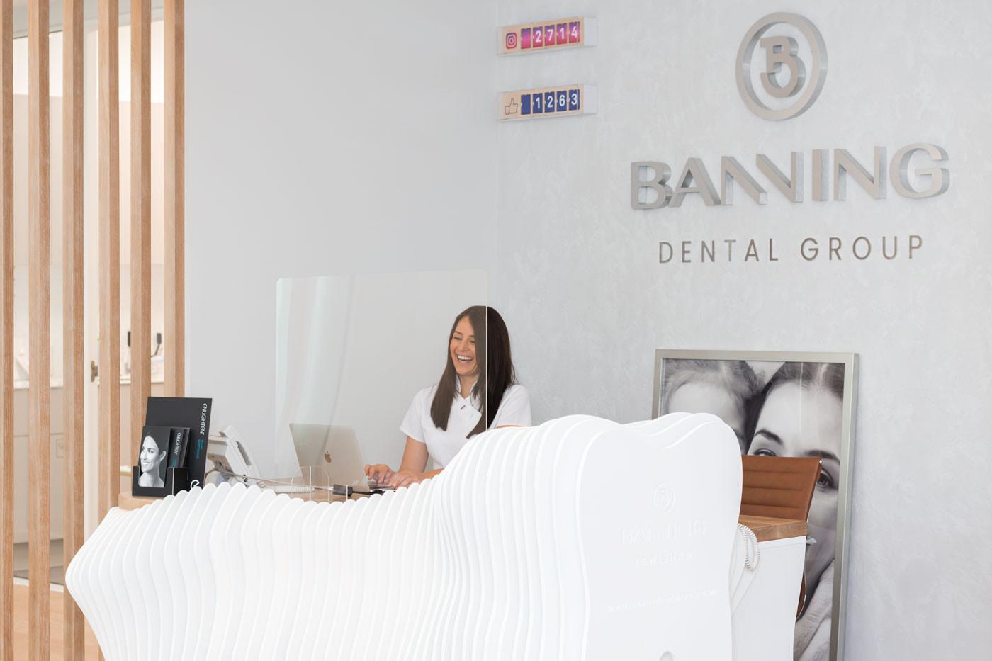 A receptionist smiling whilst sitting behind the bespoke reception desk at Banning Dental Group Lewisham