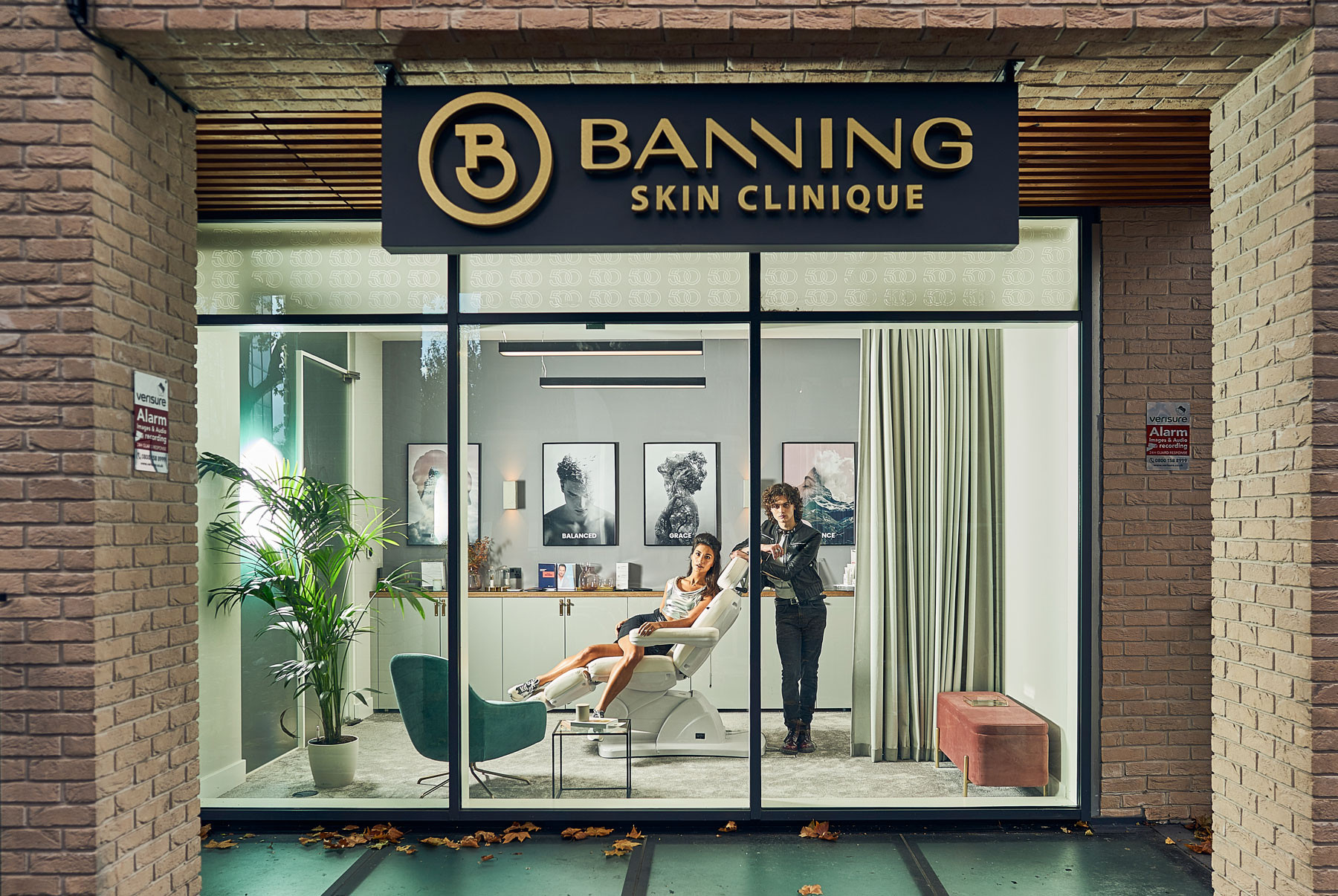 Exterior of the Banning Skincare Clinque taking during the evening with the lights on inside showcasing the design with 2 models one lady laying on the chair and a man standing beside her