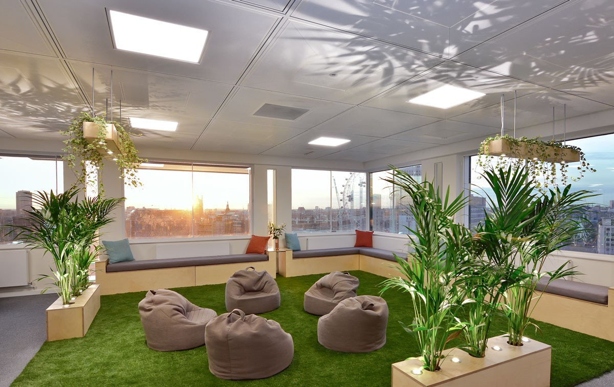 A communal interior garden at the InfoTrack office with artificial turf surrounded by exotic palm plants with comfortable pouffes and benched seating areas