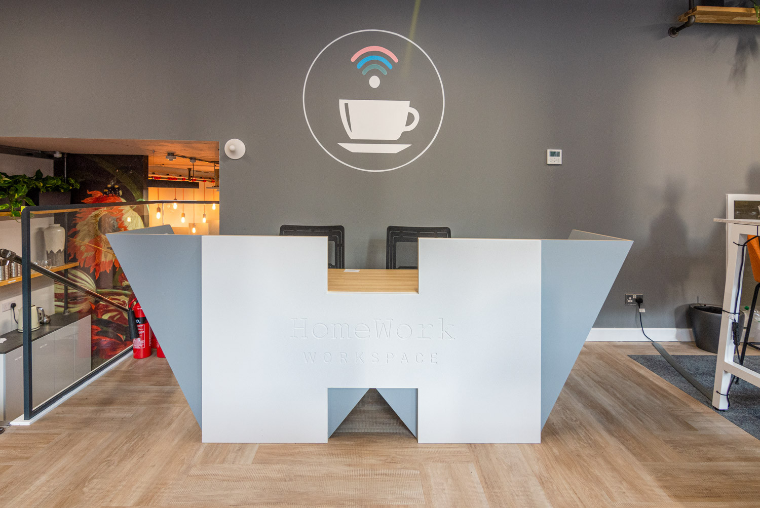Bespoke branded reception desk that combines the letters of the logo.