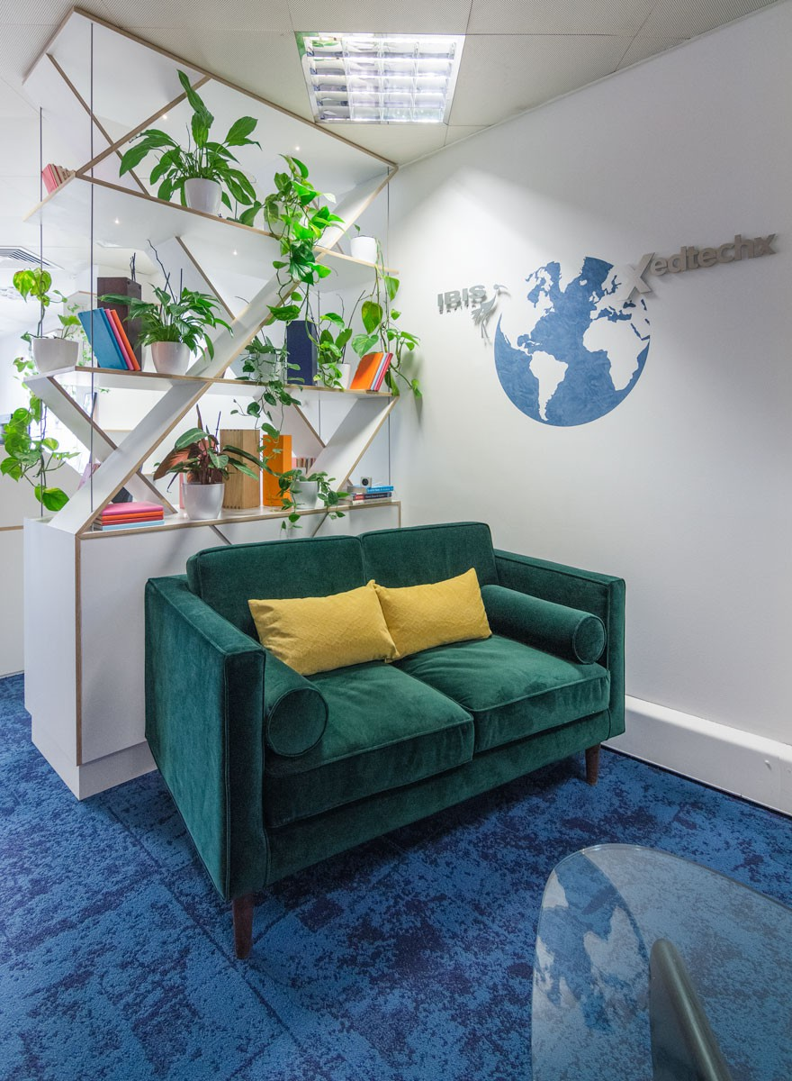 The main reception area design at the Ibis office with a green velvet sofa and 2 yellow cushions, blue textured carpets and bespoke shelving units
