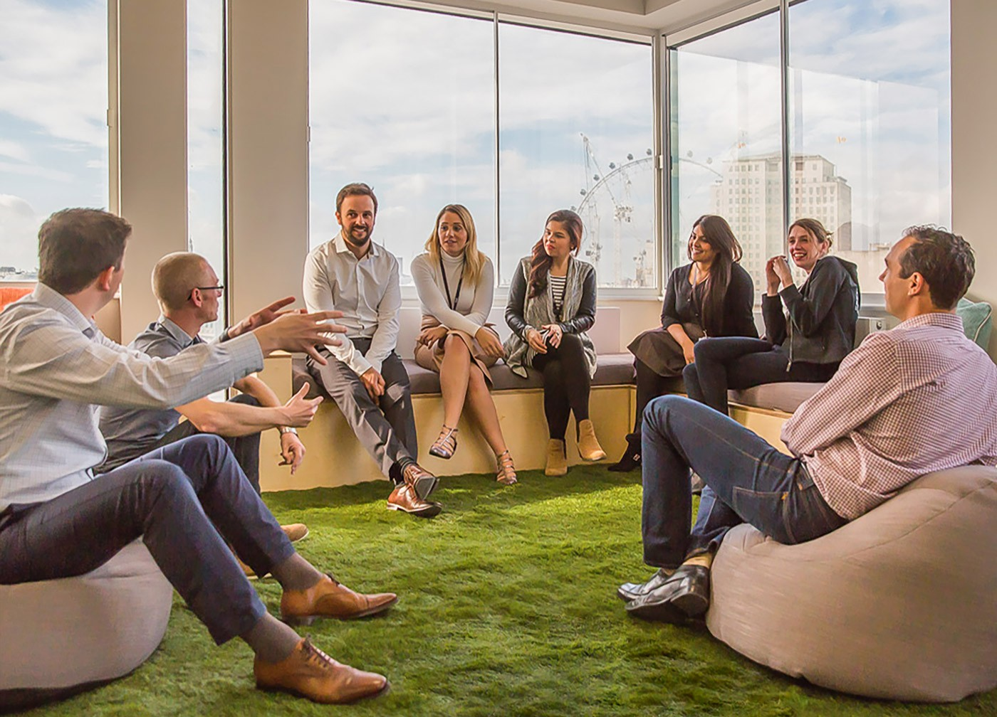 InfoTrack team using the breakout area garden design for a team meeting sitting on the benches and pouffes with a window view overlooking the London Eye.