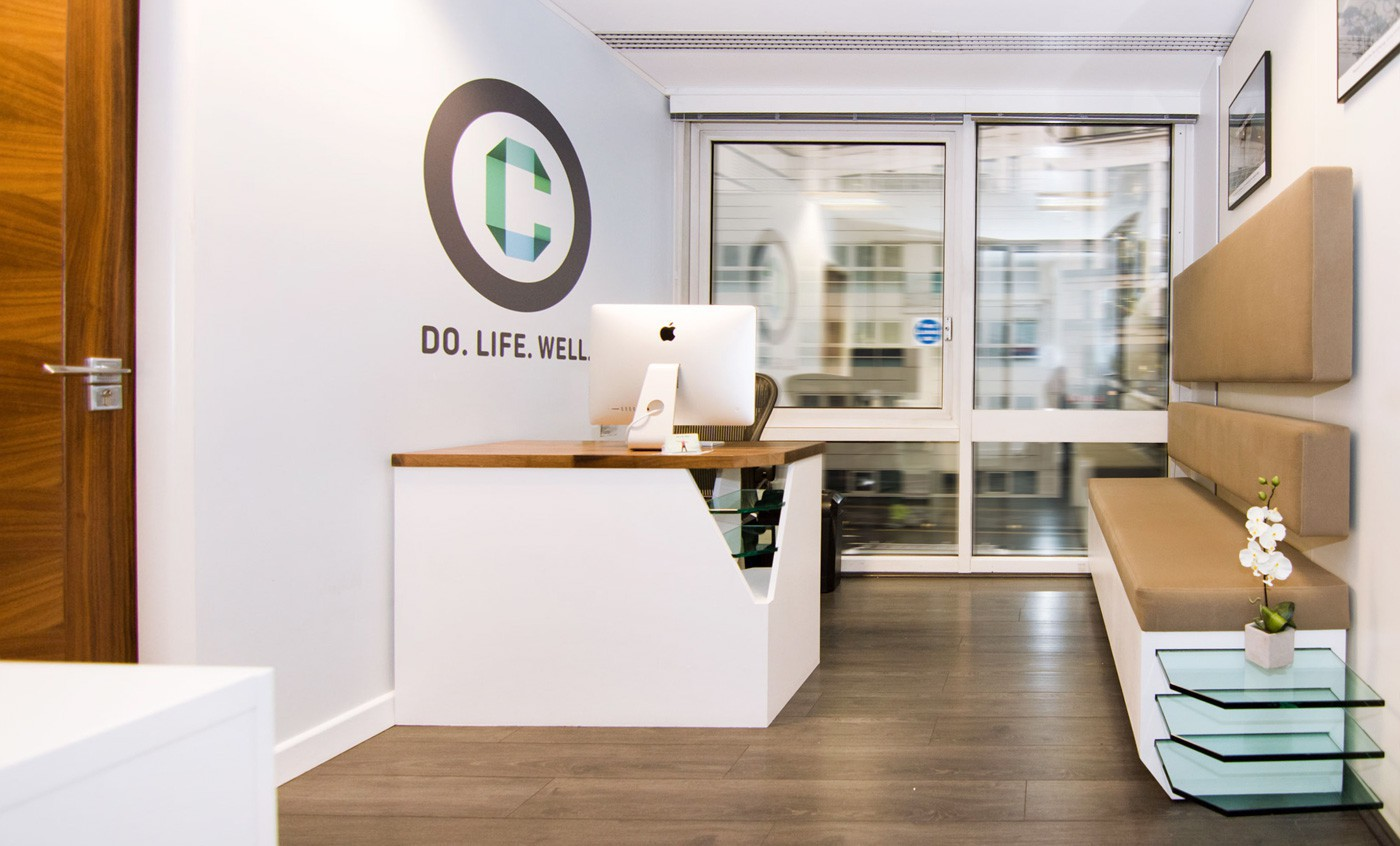 The main reception design at one of the London Doctors Clinic offices with bespoke furniture desk and banquette