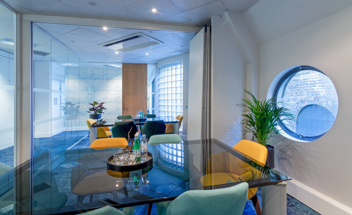 A open plan meeting room with 2 rectangular glass tables, blue and yellow chairs and flexible wall partition that can slide across to form two meeting rooms at the Ibis office