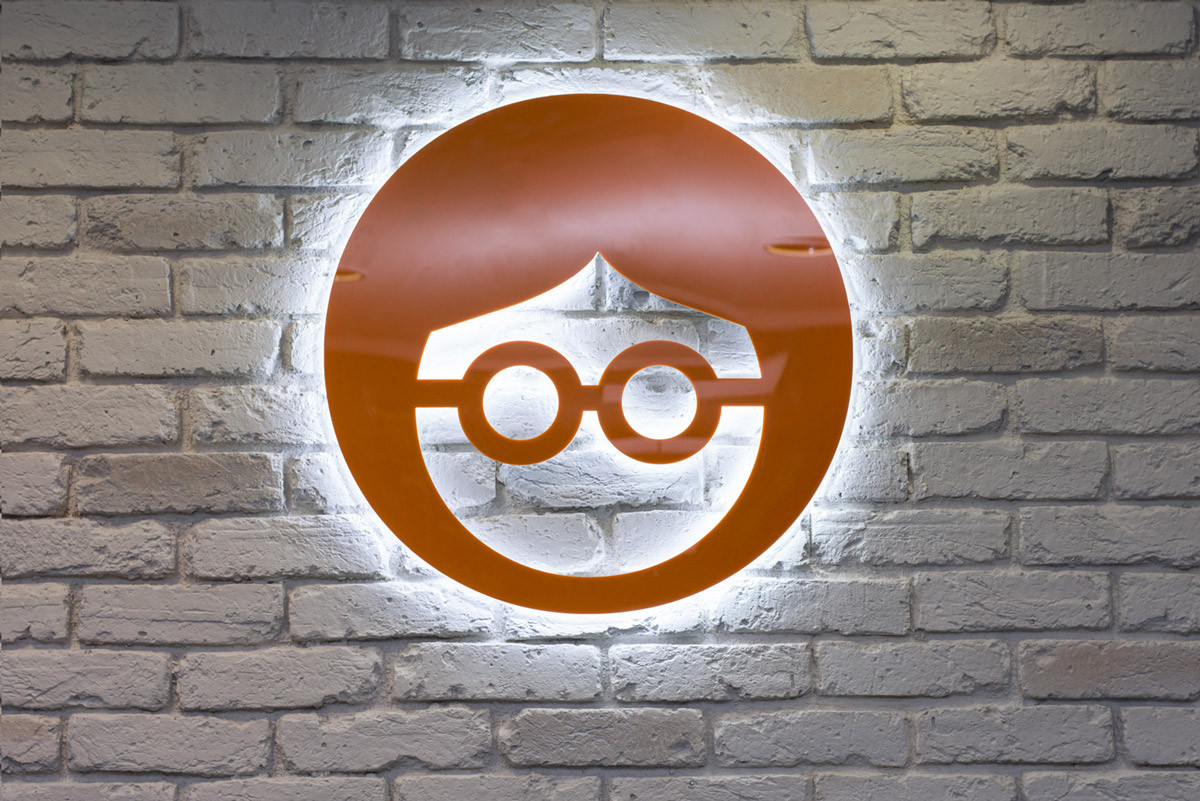 The circular Outbrain orange logo with LED illumination coming from behind mounted against a white brick wall