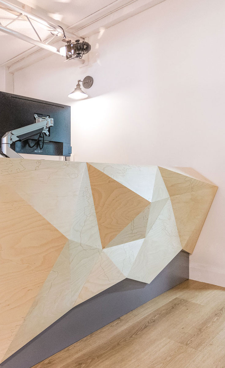 A close up detailed image of the bespoke reception desk that is abstract and dynamic.