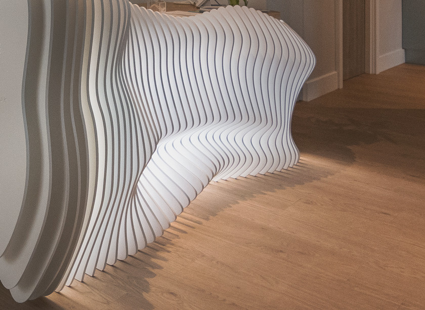 close up picture of bespoke desk for banning dental group that has organic shape of curves and light passes through the wooden slats