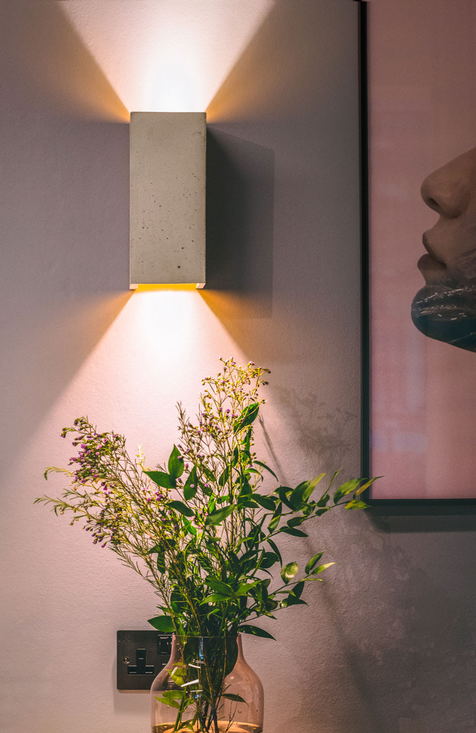 a picture of wall light within a beauty room with light shining upwards and downwards from the light