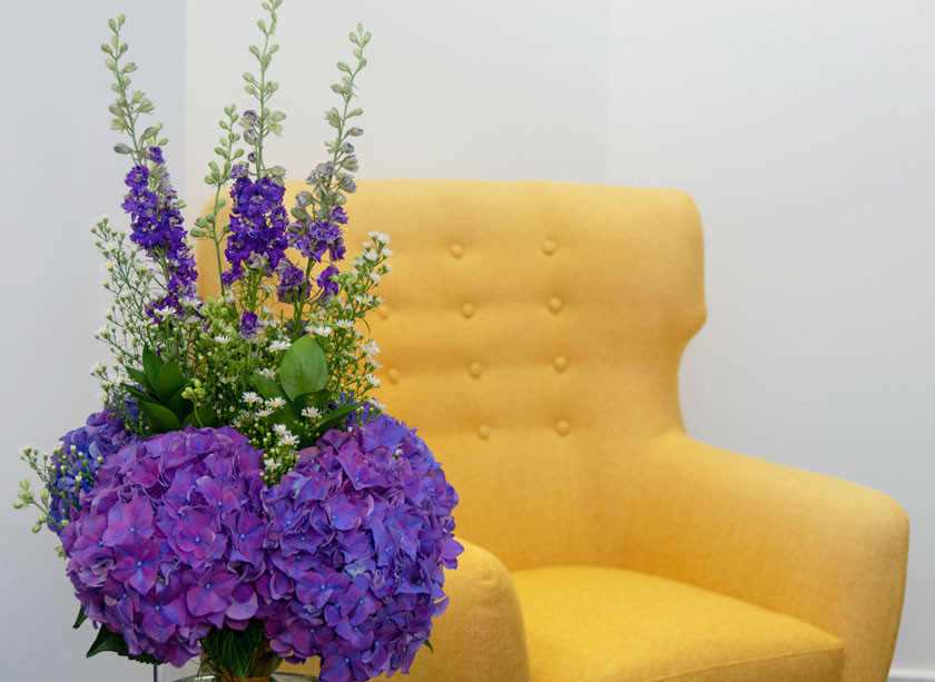 A close up of a bunch of purple flowers located on the table infront of the yellow armchair in the Ibis reception area