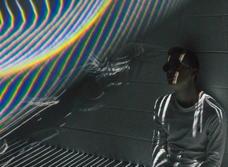 a picture of a guy with sunglasses sitting on a floor with refracted light reflection above him