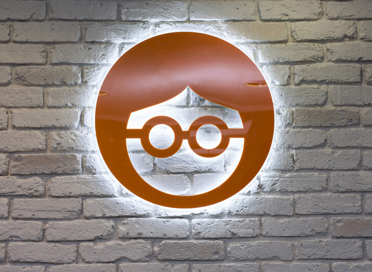 The circular bespoke Outbrain orange logo with LED illumination coming from behind mounted against a white brick wall