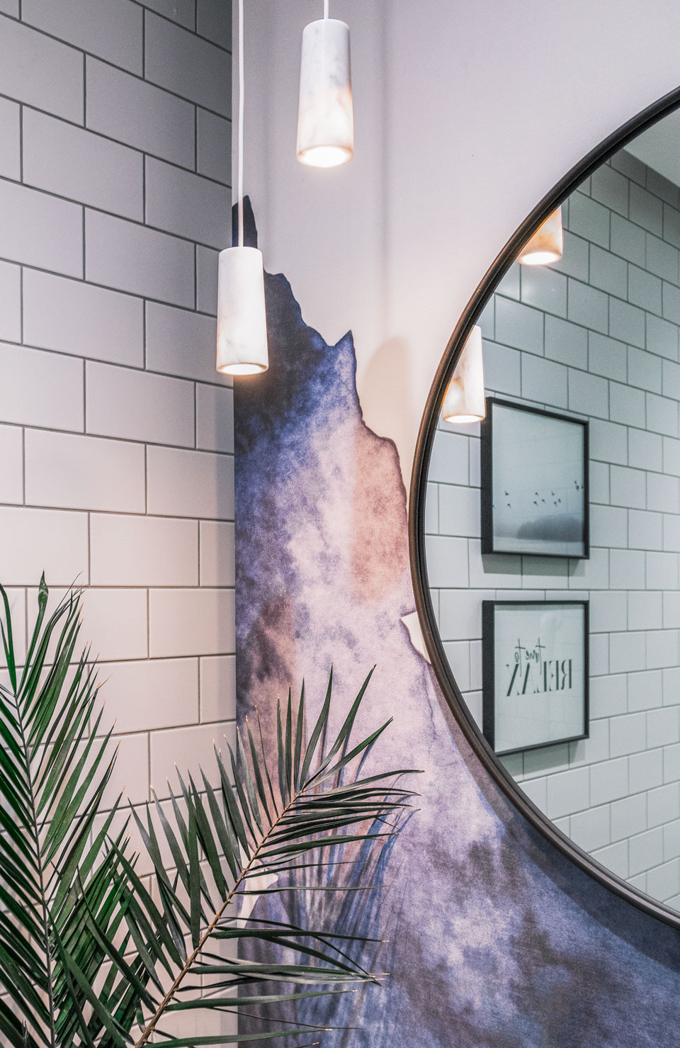 Dental office interior design with a touch of wellbeing, this vanity station at The Banning Dental Group is designed with washed out purple and blue wall colours with a circular charcoal grey framed mirror and a plant for adding nature elements into design