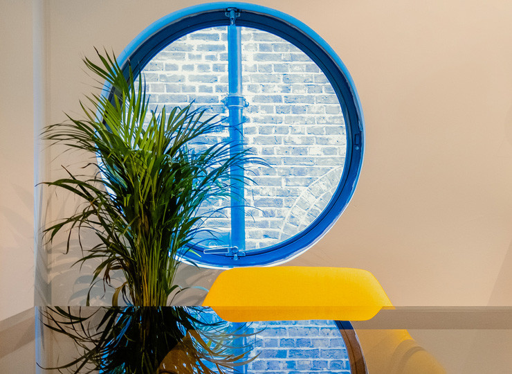 a picture of a circle window in a meeting room with a yellow chair on the left and small palm plant on the right